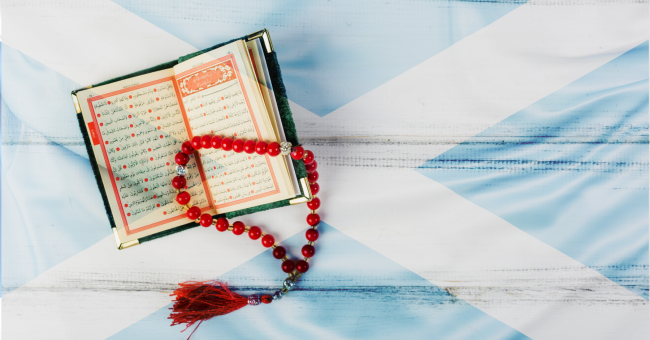 Quran opened with a faded Scottish flag as background